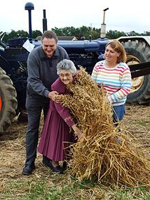 Mrs Sheila Galbally - centre - enjoys the threshing